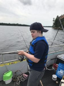 A boy in a blue life vest stands on a boat deck, fishing